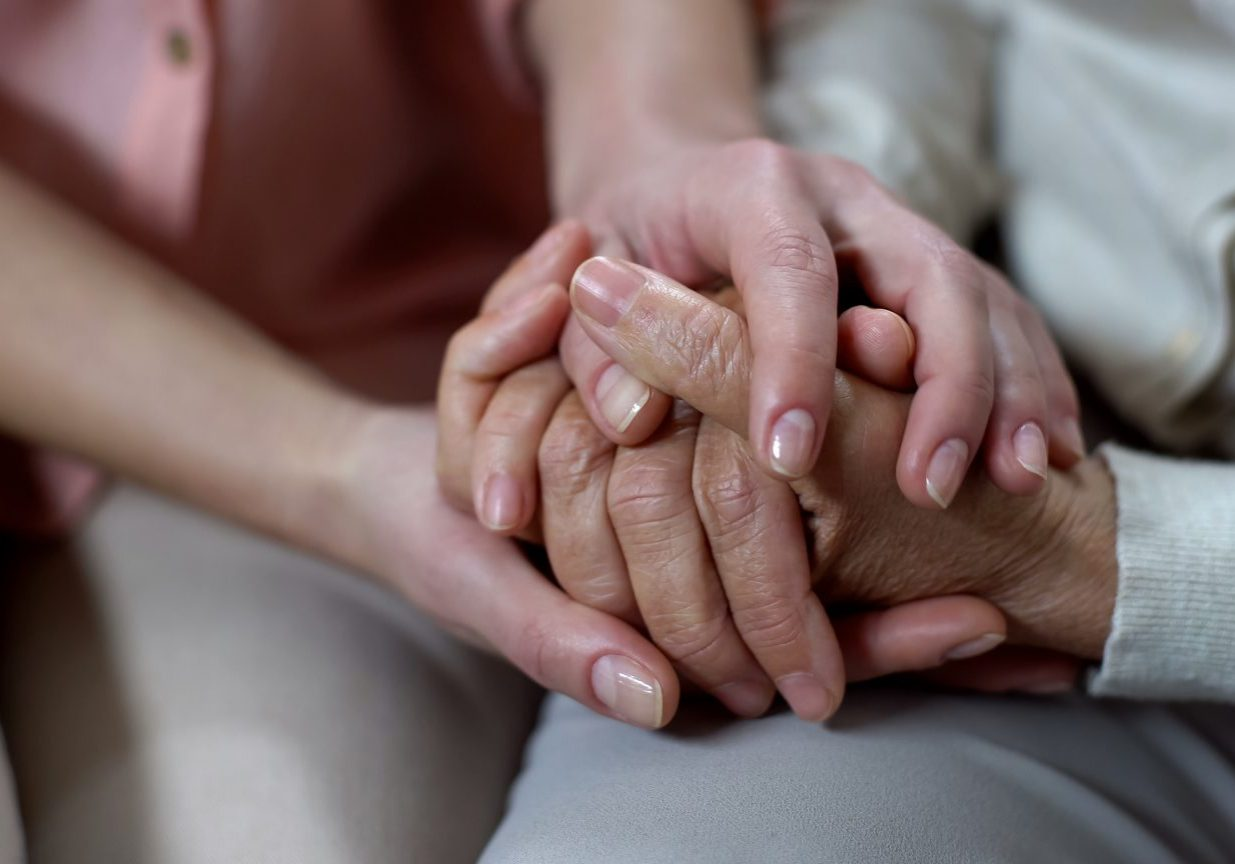 Woman holding mother hands closeup, nursing home support, family love and help